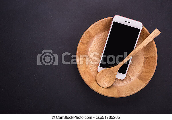 Smartphone in wooden bowl on black stone table background, concept Eating technology - csp51785285
