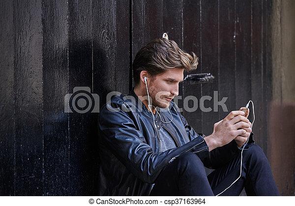 Joven escuchando audífonos de música inteligente - csp37163964