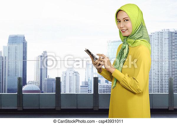 smartphone, muslim, kobieta, asian, używając, uśmiechanie się - csp43931011