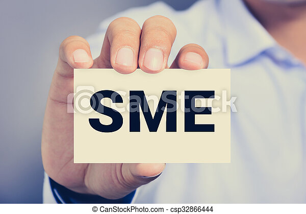 SME letters (or Small and Medium-sized  Enterprises) on the card shown by a man - csp32866444