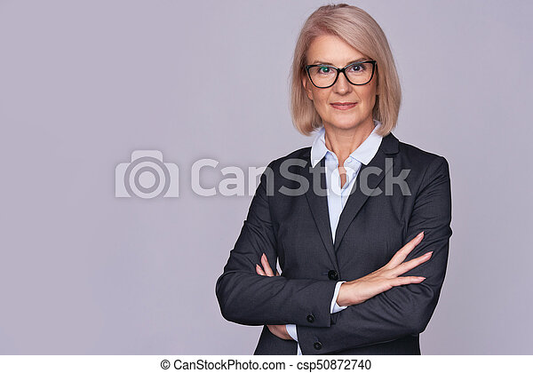 Smile senior business woman with folded hands - csp50872740