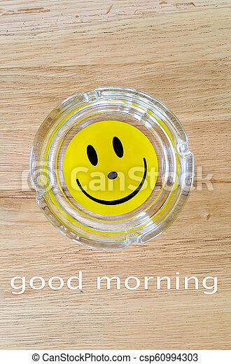Smiley Face On An Ashtrayon Wood Background With Text Good Morning