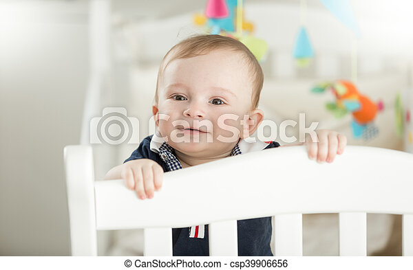 Smiling 9 month old baby standing in white wooden crib - csp39906656