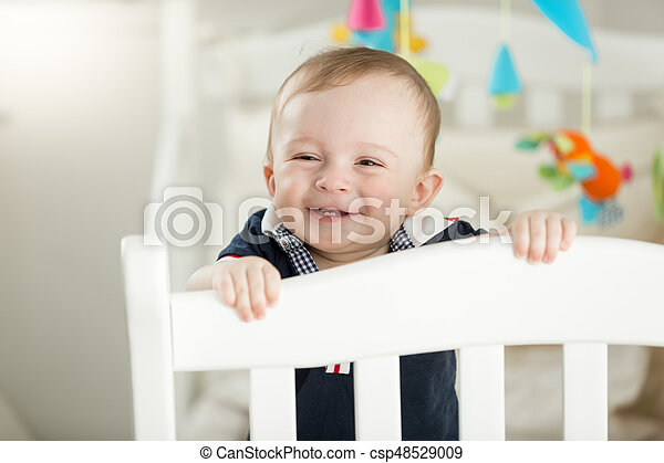 Smiling 9 month old baby standing in white wooden crib - csp48529009