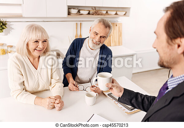 Smiling advisor enjoying conversation with aging couple of clients - csp45570213