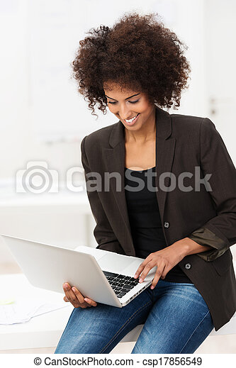 Smiling African American student using a laptop - csp17856549