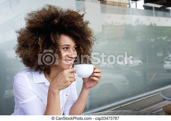 Smiling african american woman sitting with cup of coffee - csp33473787