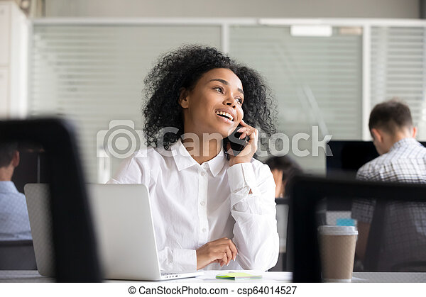 Smiling African American woman talking on phone at workplace - csp64014527