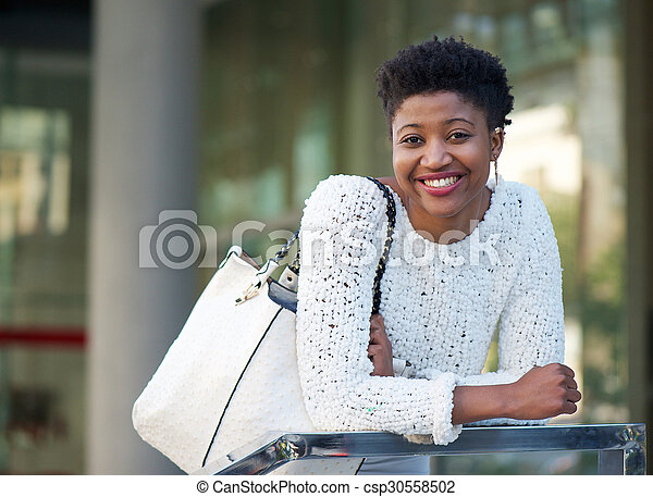 Smiling african american woman with bag - csp30558502