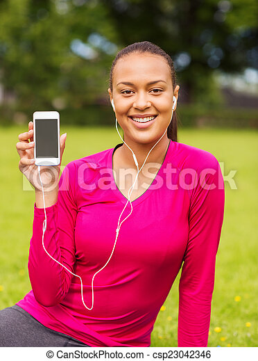 smiling african american woman with smartphone - csp23042346