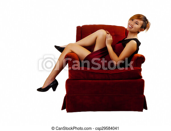 Smiling Asian American Woman Sitting In Red Dress - csp29584041