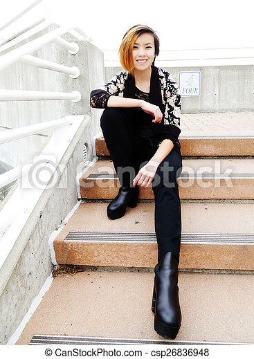Smiling Asian American Woman Sitting On Steps - csp26836948