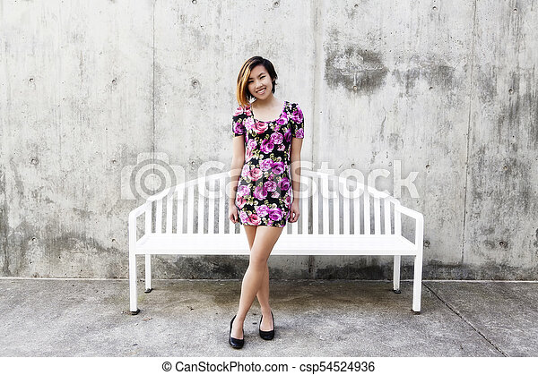 Smiling Asian American Woman Standing In Floral Dress - csp54524936