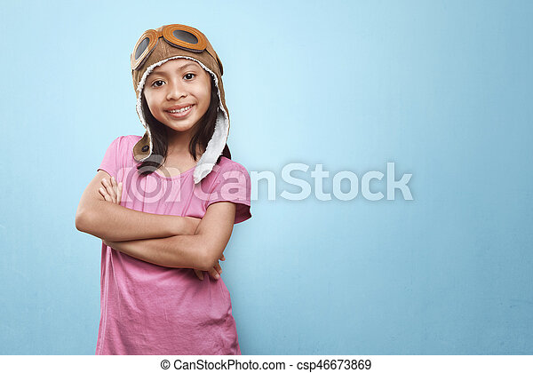 smiling asian little girl with aviator hat and goggles having fun