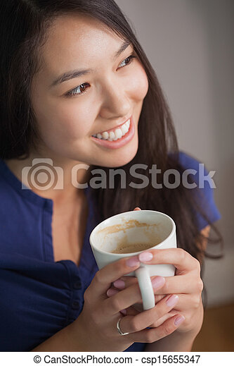 Smiling asian woman holding mug of coffee looking away - csp15655347