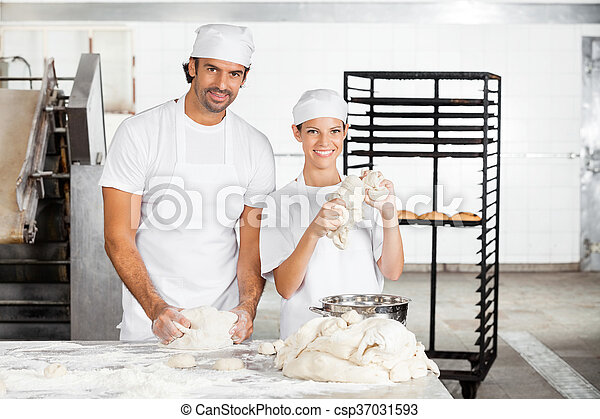 Smiling Baker's Kneading Dough Together In Bakery - csp37031593