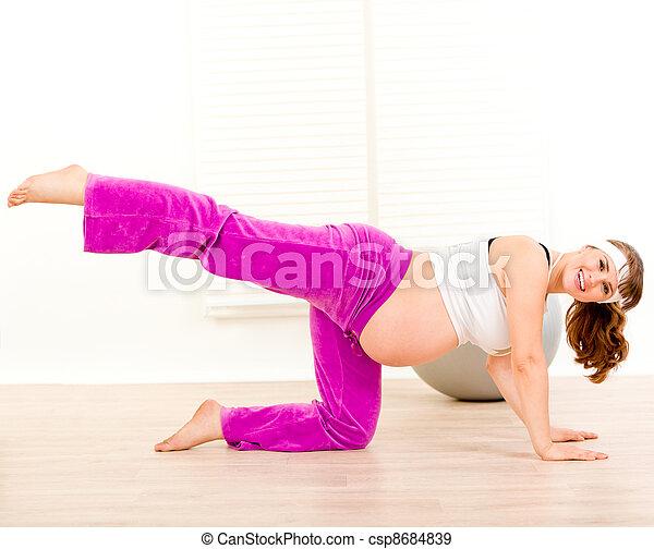 Smiling beautiful pregnant woman doing aerobics exercise aerobics  at home  - csp8684839