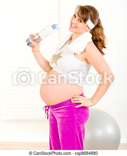 Smiling beautiful pregnant woman in sportswear holding bottle of  water