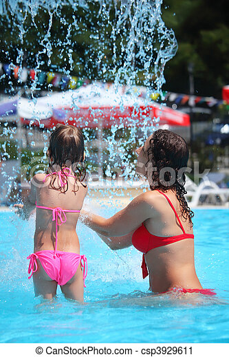 Smiling beautiful woman and little girl bathes in pool under water splashes, standing back - csp3929611