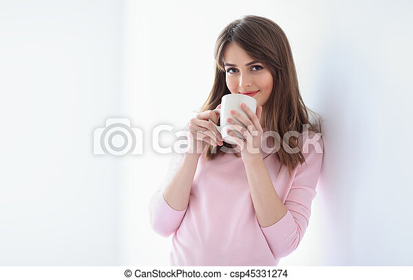 Smiling beautiful woman with cup of coffee on white background - csp45331274