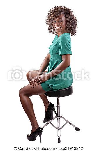 Smiling Black Woman Sitting on Stool Dress - csp21913212