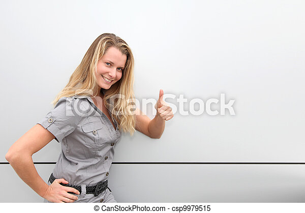 Smiling blond woman on grey background - csp9979515