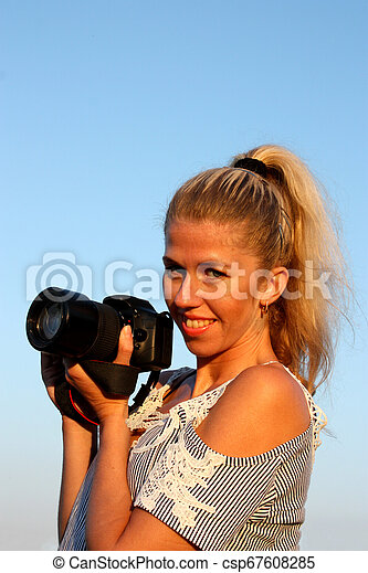 Smiling blonde girl with camera in hand. - csp67608285