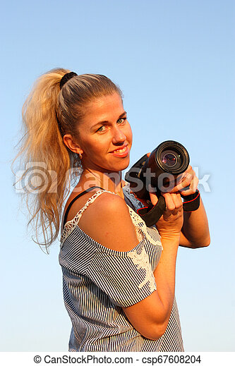 Smiling blonde girl with camera in hand. - csp67608204