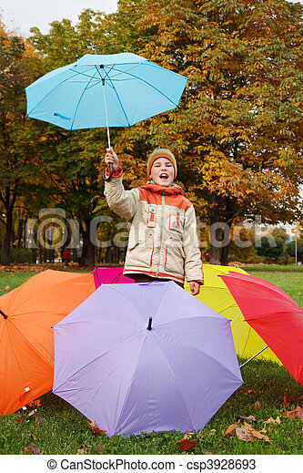 Smiling boy in autumn park. In environment of multi-coloured umbrellas. - csp3928693