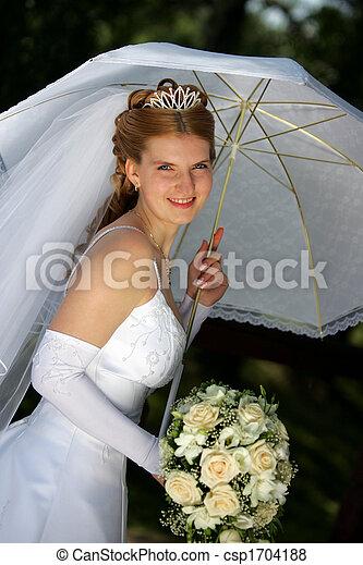 Smiling bride under parasol - csp1704188