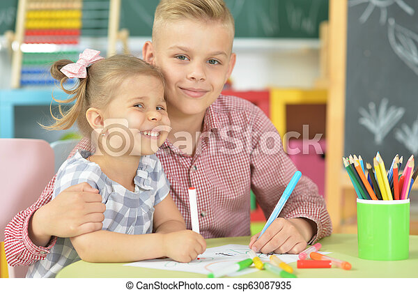 Smiling brother and sister drawing with felt pens - csp63087935