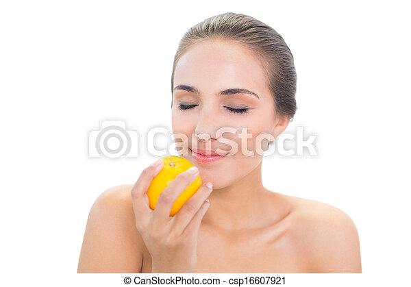 Smiling brunette woman smelling on an orange - csp16607921