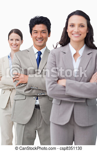 Smiling business team standing with folded arms - csp8351130