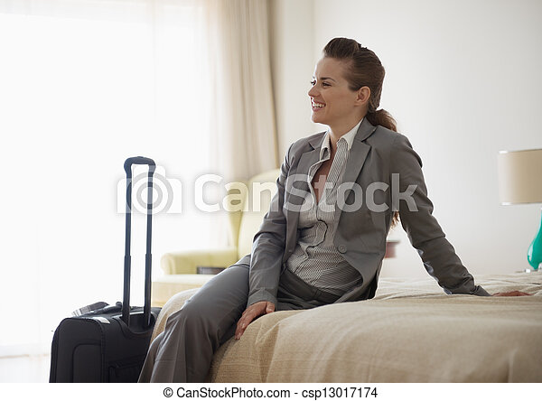 Smiling business woman sitting on bed in hotel room - csp13017174