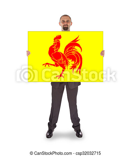 Smiling businessman holding a big card, flag of Wallonia - csp32032715