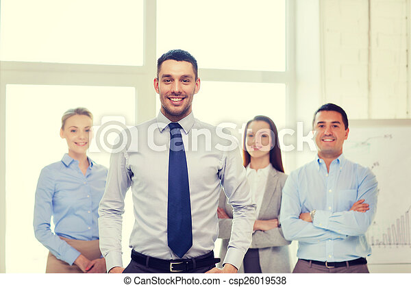 smiling businessman in office with team on back - csp26019538