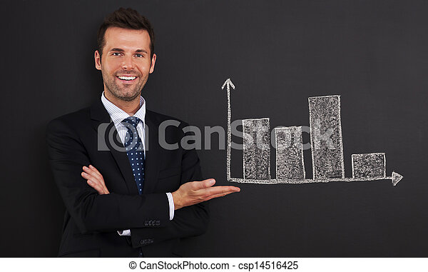 Smiling businessman presenting graph on blackboard  - csp14516425