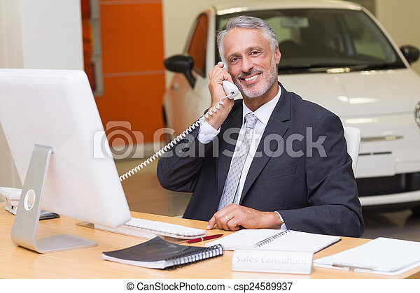 Smiling businessman using laptop on the phone - csp24589937
