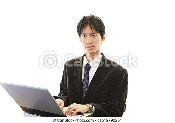 Smiling businessman using laptop - csp19790251