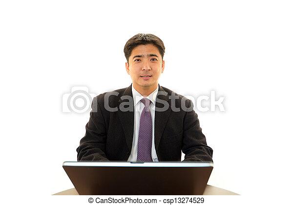 Smiling businessman using laptop - csp13274529