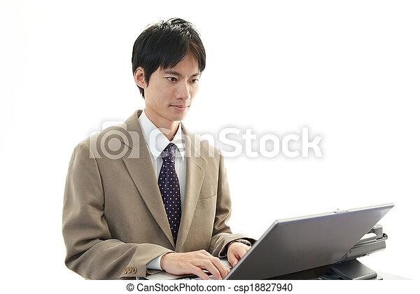 Smiling businessman using laptop - csp18827940