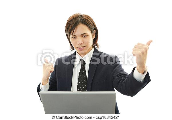 Smiling businessman using laptop - csp18842421