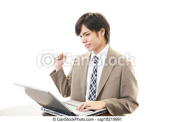 Smiling businessman using laptop - csp18219991
