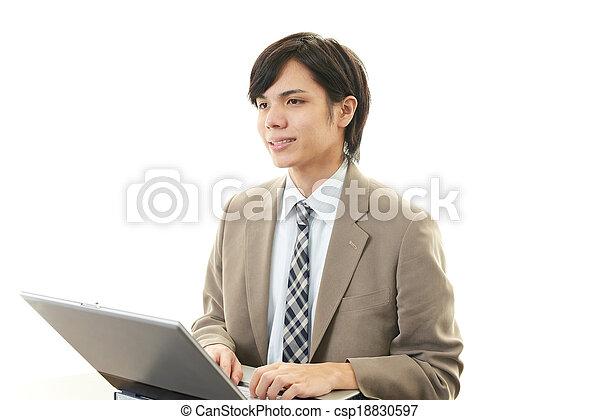 Smiling businessman using laptop - csp18830597