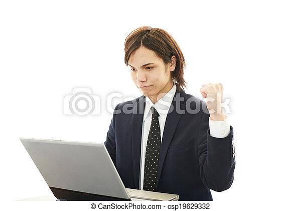 Smiling businessman using laptop - csp19629332