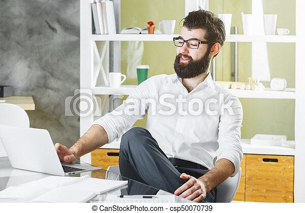 Smiling businessman using laptop computer - csp50070739