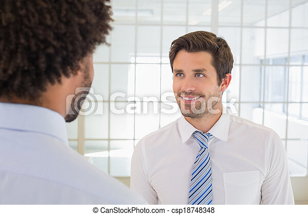 Smiling businessmen looking at each other in office - csp18748348