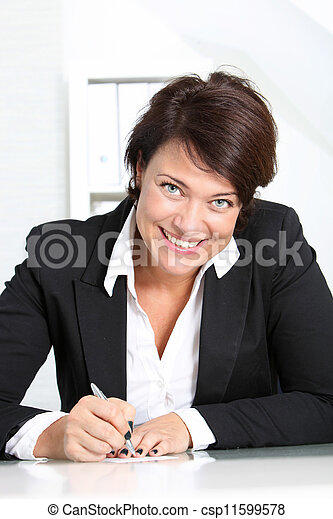 Smiling businesswoman at her desk - csp11599578