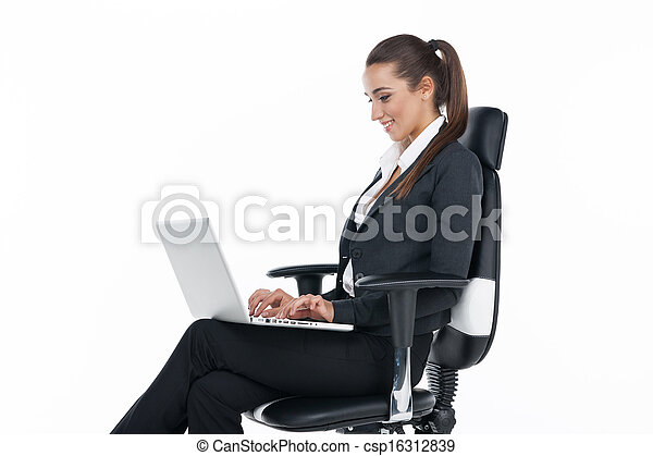 Smiling businesswoman sitting in a chair with laptop. Isolated on white - csp16312839