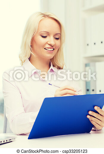 smiling businesswoman with clipboard in office - csp33205123